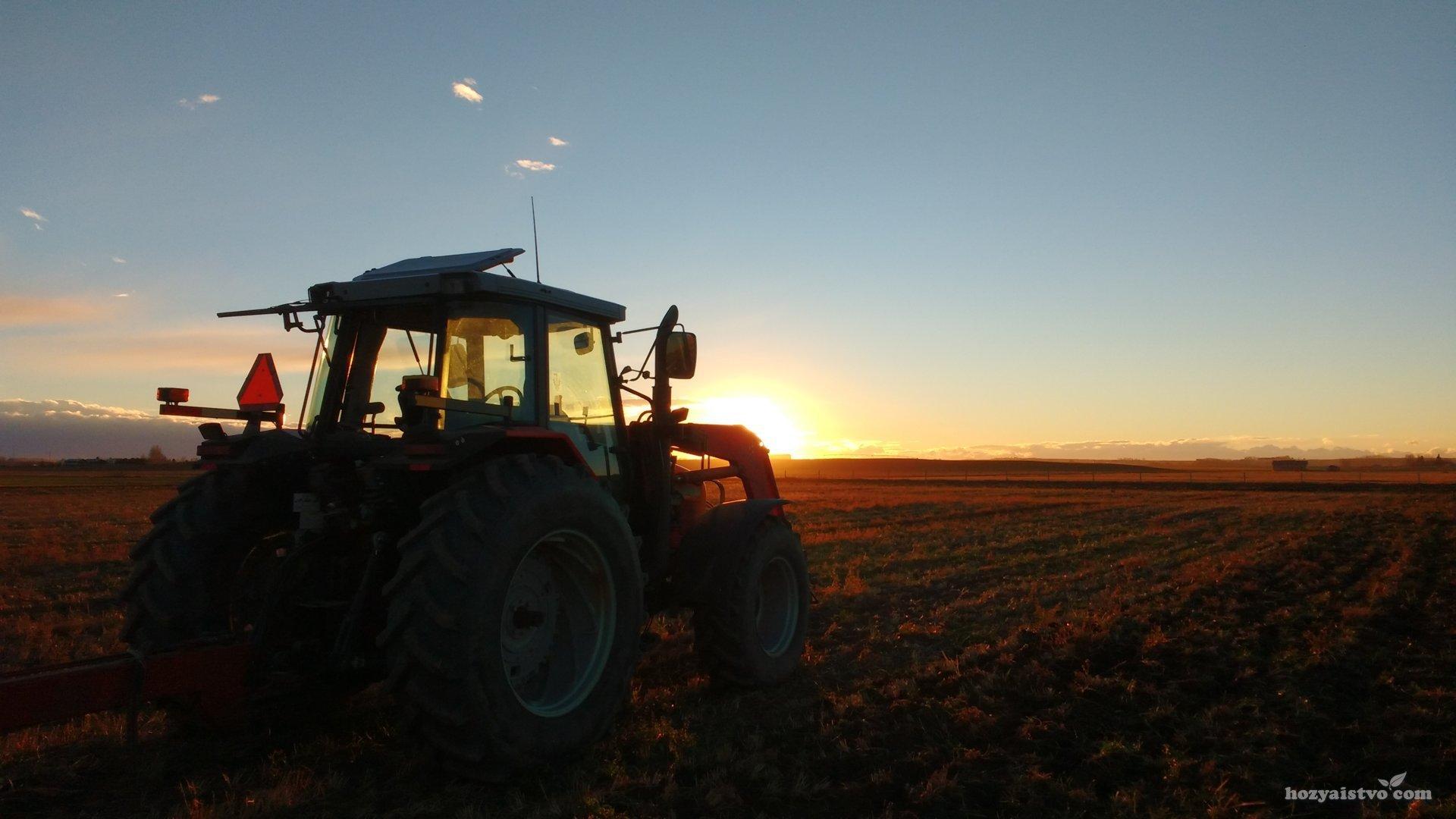 Трактор на фоне заходящего солнца